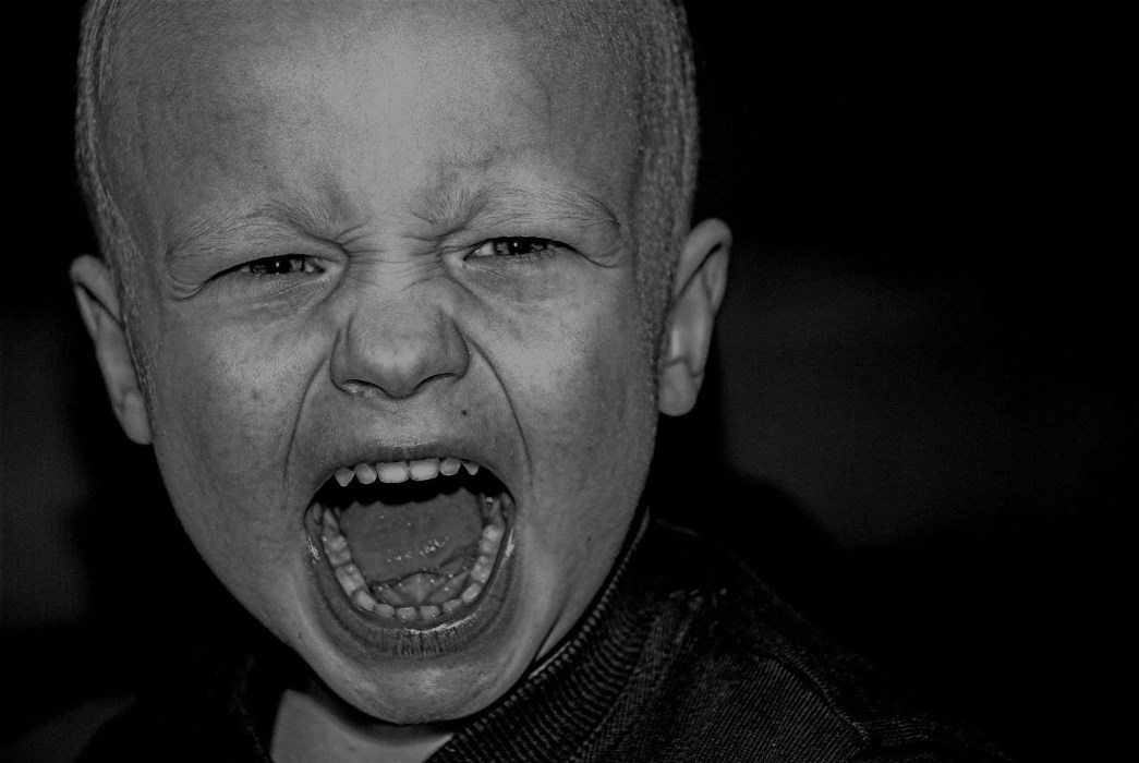 Black and white image of a child screaming
