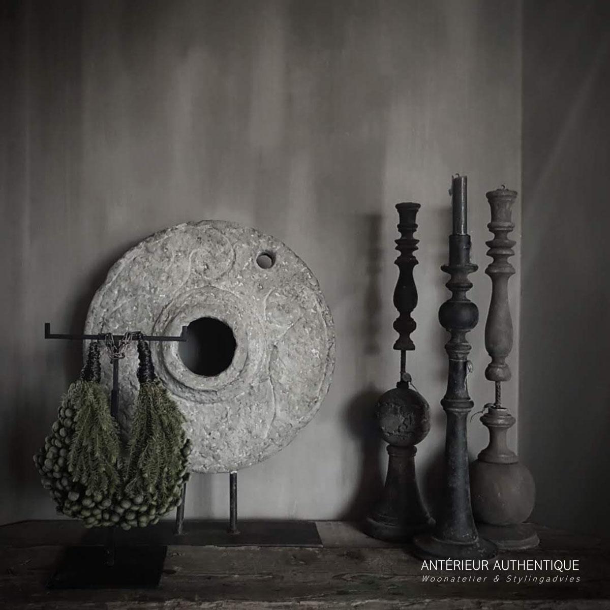 Afbeelding van molensteen ornament op statief met kaarsenstandaards en groendecoratie voor gebruik in Antérieur Authentique webshop