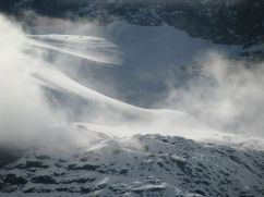 Fog forms above snow-covered mountains.