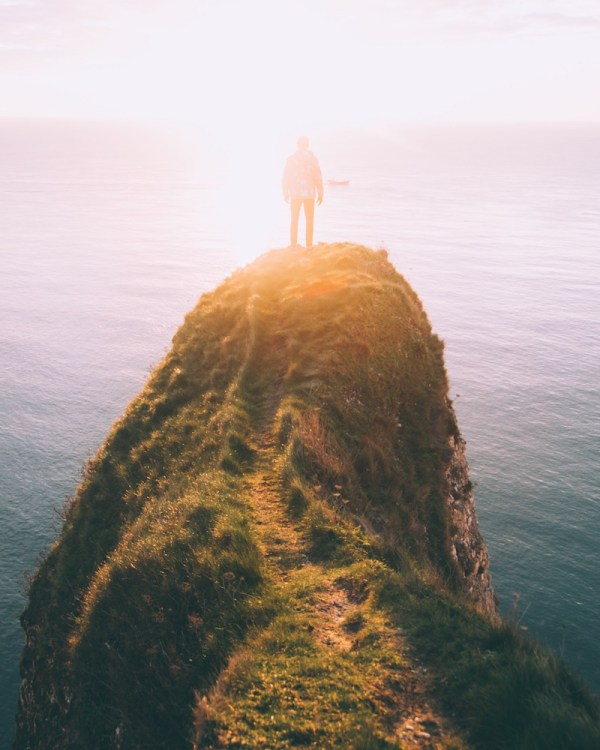 Person standing on a rocky promontory, high above the sea, facing the sun