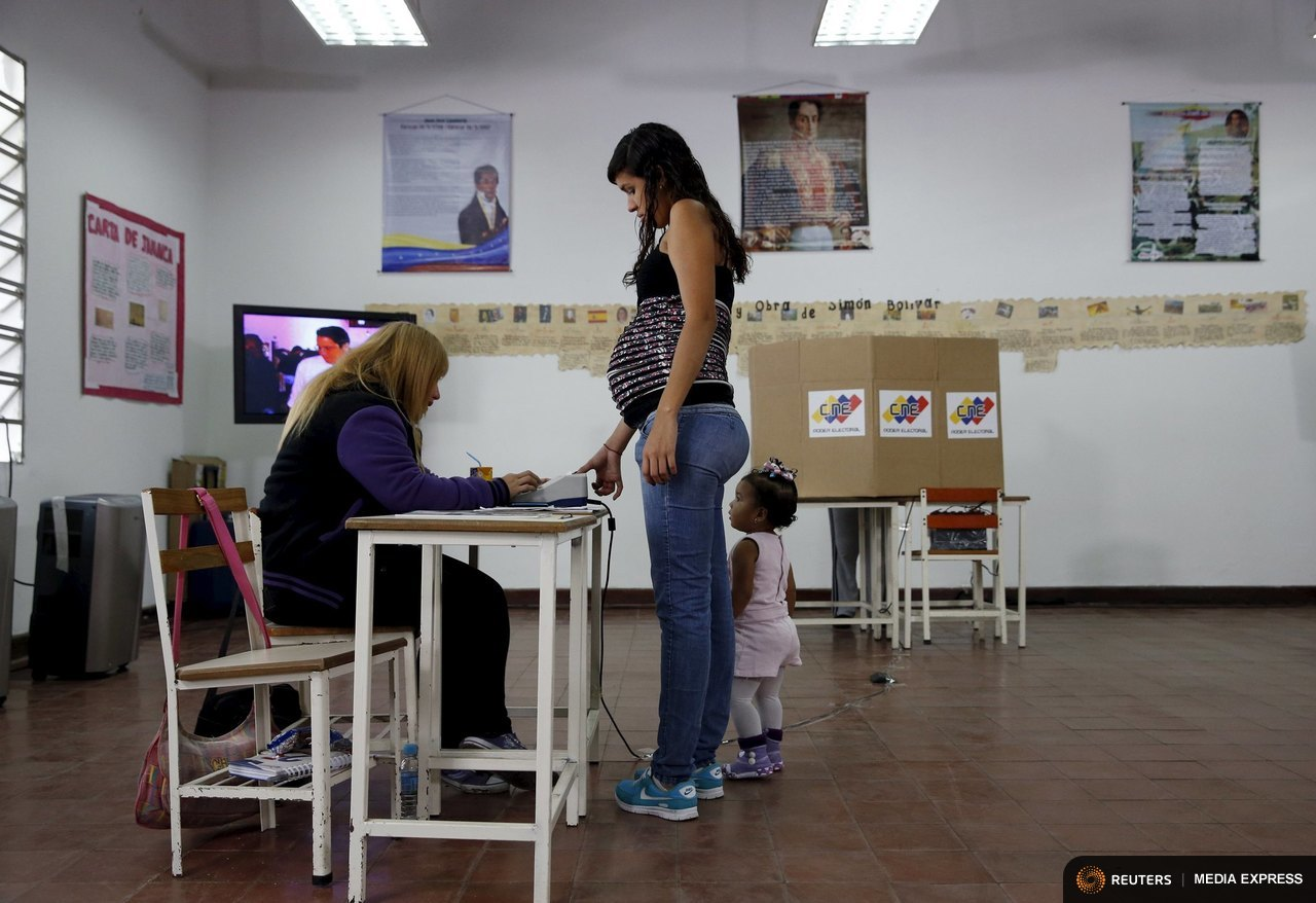 A woman registers before casting her vote at a polling station during a legislative election, in Caracas December 6, 2015. REUTERS/Carlos Garcia Rawlins