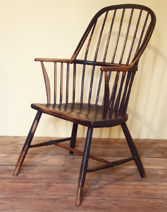 The standard hoop-back design, in ash, with the armrest and back each bent from a single piece. Similar in design to those made in the West Country, these were common in the Towy valley where they were produced in family workshops by specialist chairmakers. This has been painted several times and the different layers of red, blue and black have been worn through with regular usage. Carmarthenshire, c. 1780-1820. Writer's collection