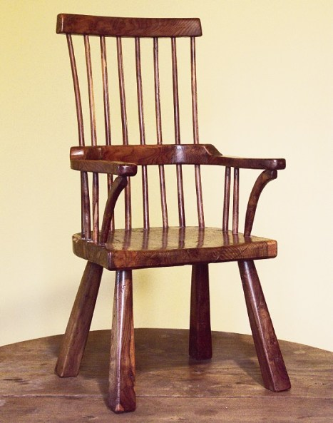 """Standing just 59cm (22in) tall, this child's yew-wood chair is inscribed under the seat with the maker's initials """"JKWW"""". Pembrokeshire, possibly late 19th century."""