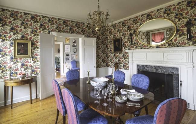 Jayne enlivened Chandler Farm's dining room with a bright, historic print from Adelphi Paper Hangings and covered reproduction dining chairs with printed linen in contrasting shades of cobalt and raspberry. Photo James Schneck.
