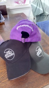 3 caps stacked. 2 bottom caps are black and green facing forward showing the AntnzVentures logo. Top purple caps shows the back with #ThriveNotSurvive