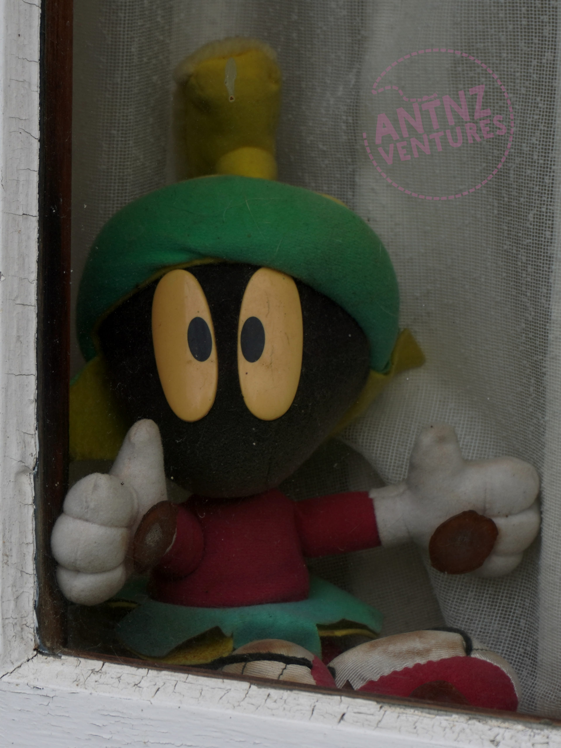 A stuffed Marvin the Martian. Marvin is sitting on a windowsill, behind glass but in front of a net curtain.