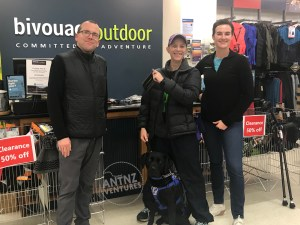 Antnz with 2 staff members from Bivouac Outdoors, Palmerston North in front of the counter. Antnz is holding a waterproof phone case. Antnz' elbow crutches can be seen to the side of them. ADNZ Raven is sitting in front of Antnz