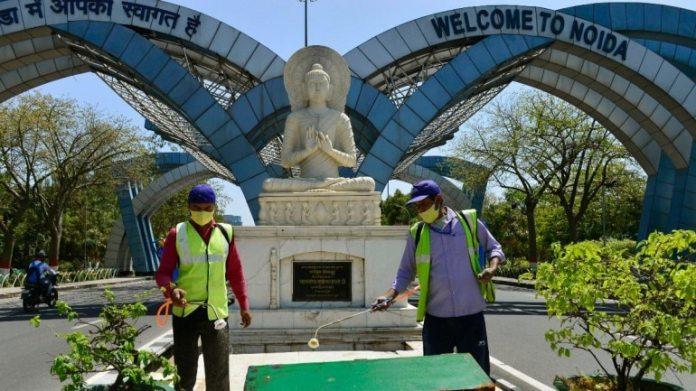 नोएडा सीमा पर मूर्ति की सफाई करते सफाई कर्मचारी