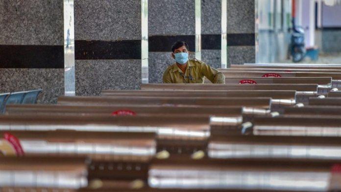 एक कार्यकर्ता गुरुवार को दिल्ली के निजामुद्दीन रेलवे स्टेशन के एक सुनसान मंच पर बैठता है। (फोटो: पीटीआई)