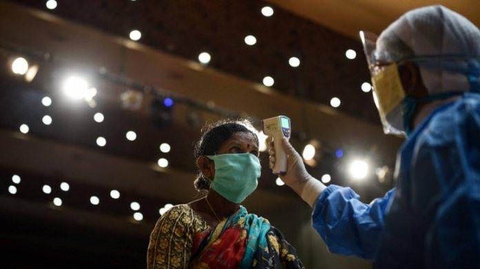 6 जून को विजयवाड़ा में कोविद -19 के लिए नि: शुल्क स्वास्थ्य जांच शिविर के दौरान एक सफाई कर्मचारी का दवा तापमान जांचता है