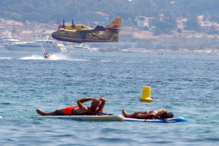 17 अगस्त, 2021 को फ्रांस के सेंट ट्रोपेज़ की खाड़ी में वार क्षेत्र में लगी एक भीषण आग को बुझाने के प्रयासों में मदद करने के लिए पानी से भरे जाने के बाद एक कैनेडायर विमान के उड़ने के बाद लोग बोर्ड पर तैरते हैं। रॉयटर्स/एरिक गेलार्ड