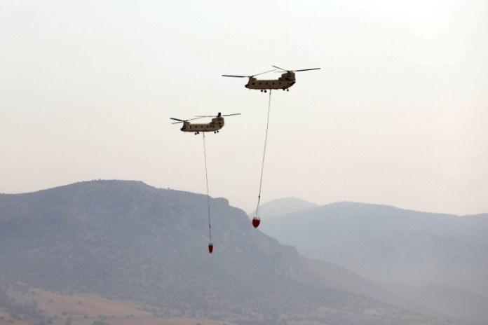 मिस्र के दो चिनूक हेलीकॉप्टर एलेफ़्सिना मिलिट्री एयर बेस के ऊपर से उड़ान भरते हैं, ग्रीस में अग्निशामक सहायता प्रदान करते हैं, अगस्त ११, २०२१। REUTERS/Louiza Vradi