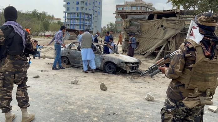 काबुल, अफ़ग़ानिस्तान में ३० अगस्त, २०२१ को अफ़ग़ान लोग एक वाहन की तस्वीरें लेते हैं जिससे रॉकेट दागे गए थे, क्योंकि तालिबान सेना पहरा देती है। REUTER/Stringer