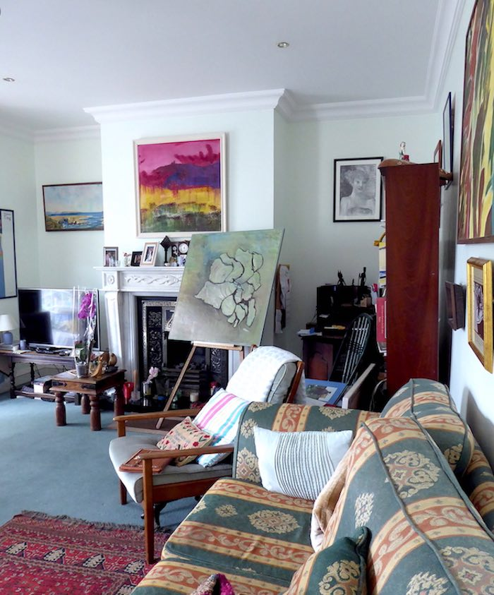 living room with paintings and easel