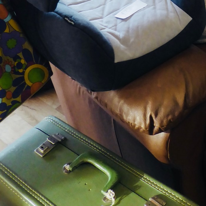 sofa and suitcase for sale in charity shop