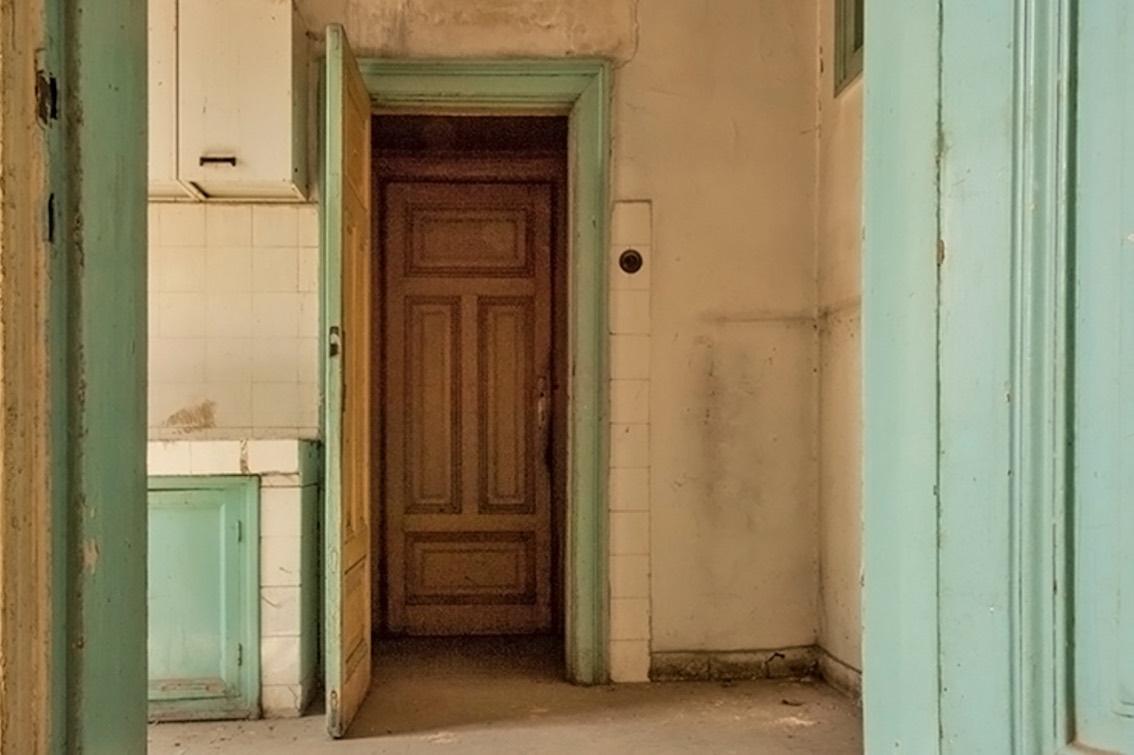 view through green doorframe to old kitchen
