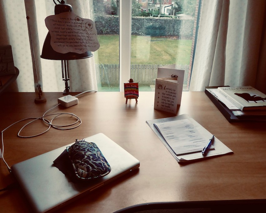desk with laptop and lamp by window