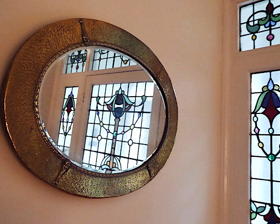 oval brass mirror reflecting stained glass in door