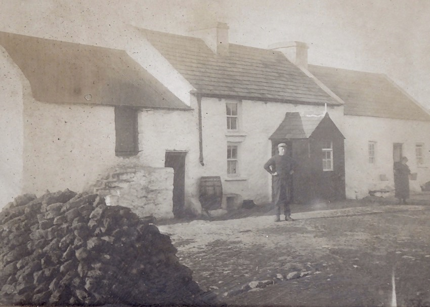 old photo of Donegal house with two people and turf stack