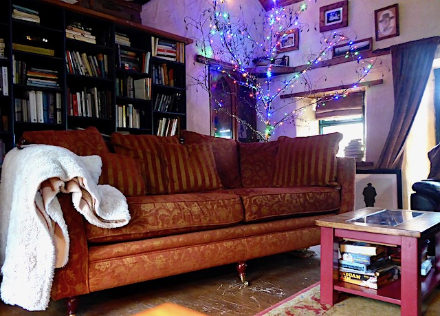large orange sofa in country house with fairly lights in tree