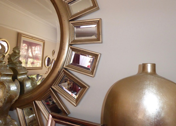gold mirror and vase reflecting room