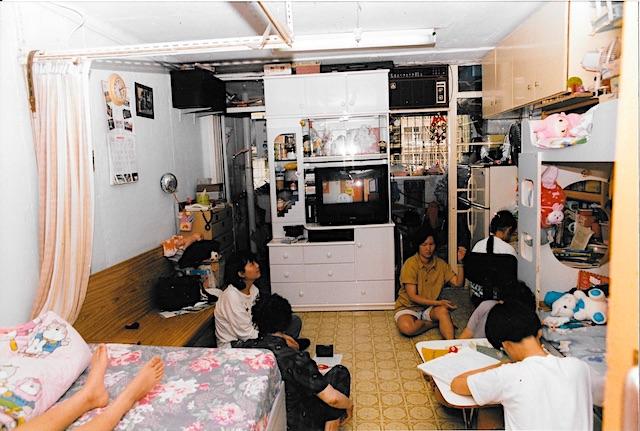 3 women sitting on floor 2 children doing homework