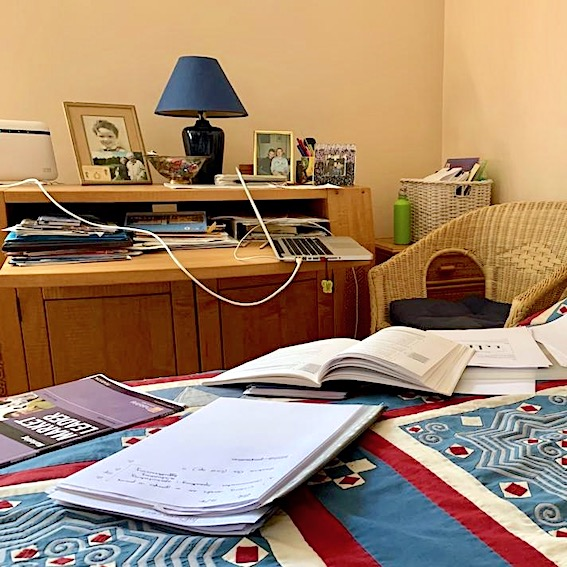 desk with papers on bed