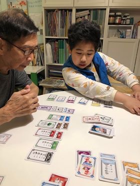 Boy and grandfather playing cards