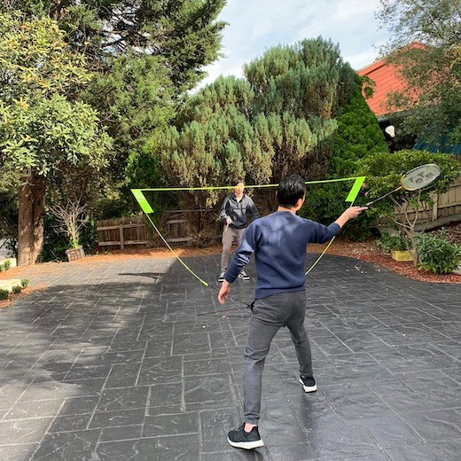 family playing badminton in garden