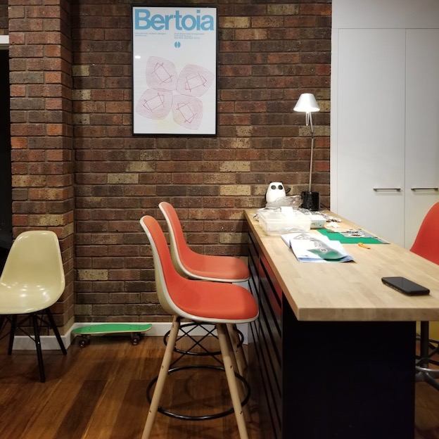 Dining table with orange chairs and brick wall