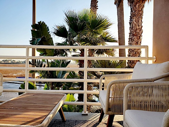sunny balcony with 2 chairs and palm trees