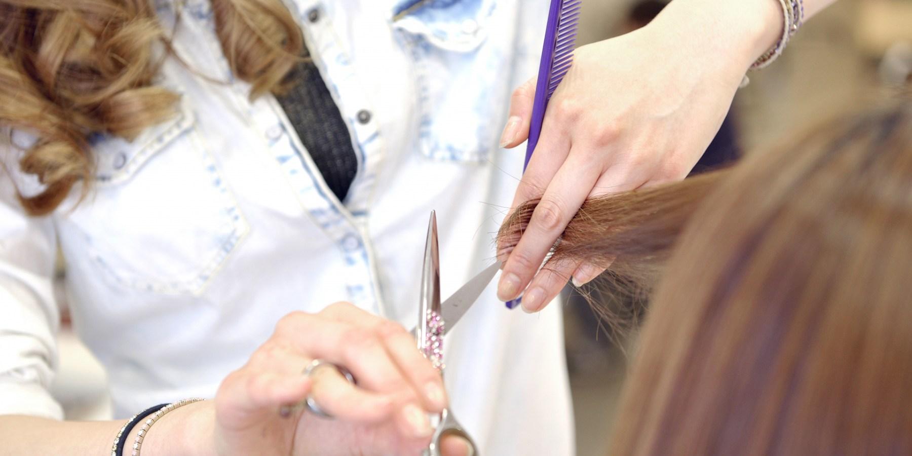 美容院で髪を切ってもらう女性の写真