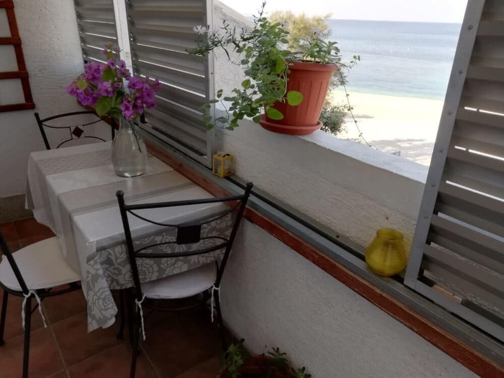 Balcony with table and three chairs and seaview at Mala Raduča in Apartmani Smiljana in Primošten