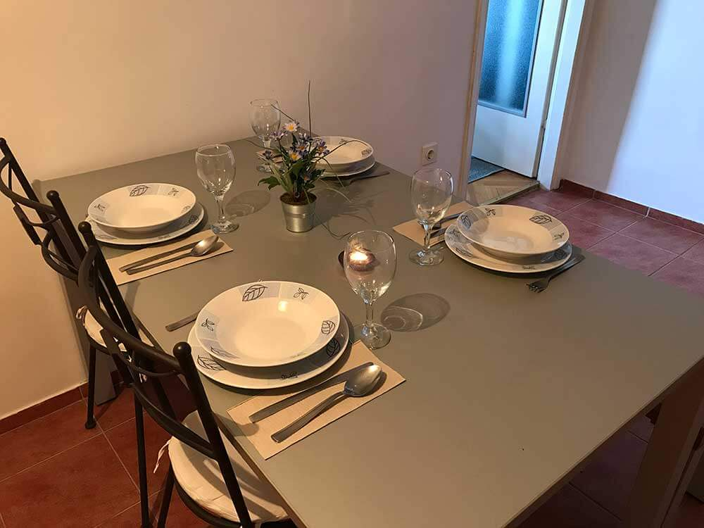 Dining table with plates, glasses and cutlery in Apartment 1, Apartmani Smiljana in Primošten
