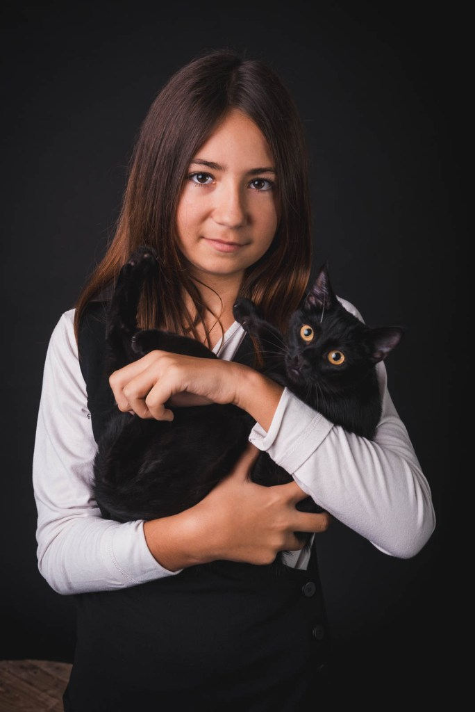family portrait of a girl with her black cat