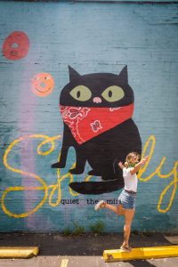 Woman in white shirt jumping in front of a large wall mural with a cat wearing a bandana