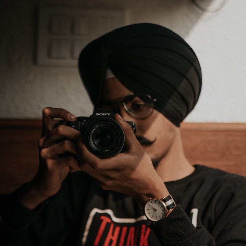 Man in a black shirt and black turban plays with a Sony camera.