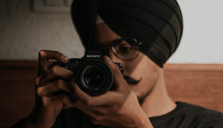 Muslim Man in a black shirt and black turban plays with a camera.