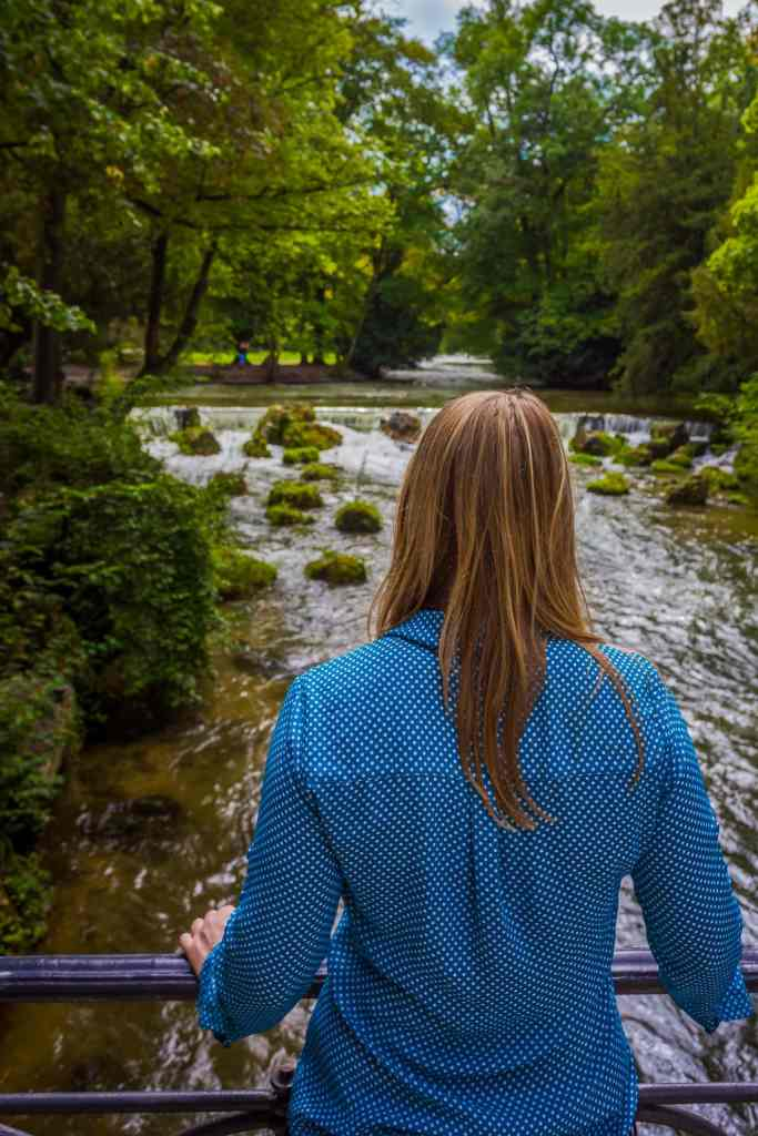 Blonde woman travelling alone over looks a small waterfall in a park.