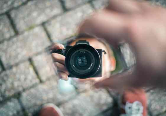 Person holding a small mirror reflecting a camera.