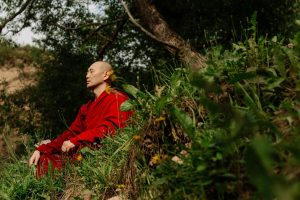 Monk in red robe meditating in a field of grass