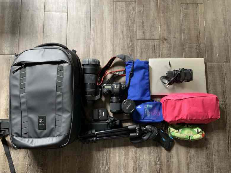 Large carryon size backpack with a DSLR camera, 3 lenses, a tripod, a laptop, and clothes