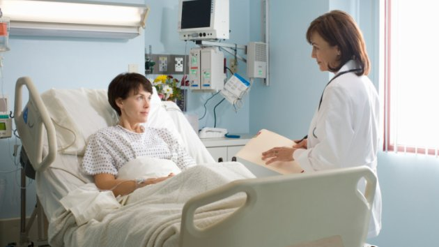 "alt=""Female doctor talking to female patient lying in hospital bed"""