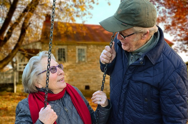 Older man standing next to his wife who is sitting in a swing