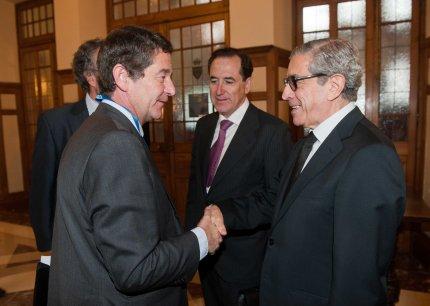 Mario Armero, vicepresidente de ANFAC, saluda a Braulio Medel a su llegada al Curso de Verano de la APIE, en presencia de Antonio Huertas, presidente de MAPFRE.