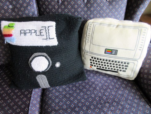 A floppy disk pillow next to the Apple II pillow.