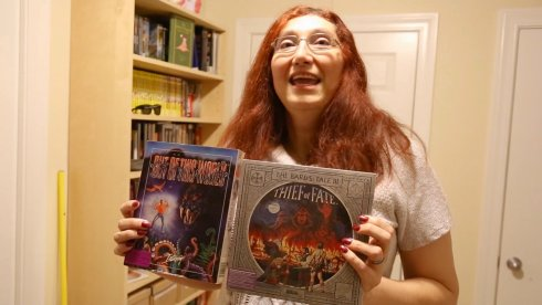 Burger Becky holding up two game boxes
