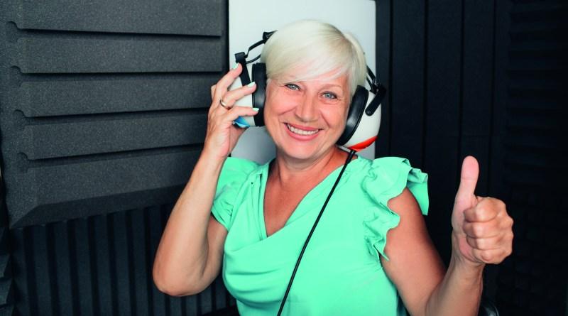 Ältere Frau mit großen Kopfhörern lächelt und hält Daumen hoch. Hörverlust Ursachen