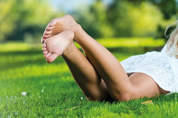 Frau in weißem Kleid liegt auf Wiese am Bauch und winkelt Füße ab. Schöne, weiche Füße.