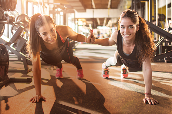 Zwei glückliche Frauen im Fitnessstudio beim Sport. Magnesiumbedarf Sportler